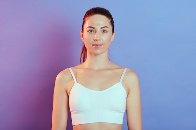 Athletic lady sporty girl in white tank top, posing after workout exercises and looking directly at camera, has ponytail, standing against color wall.