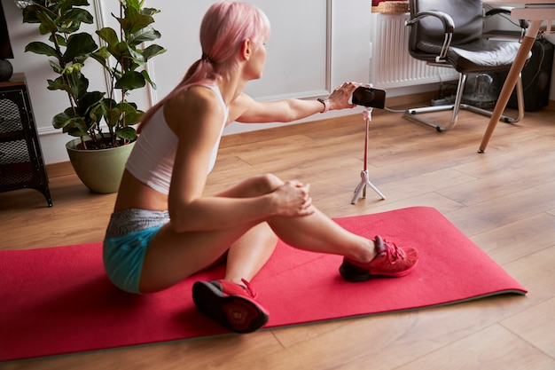 ピンクの髪のアスレチック女性が自宅でビデオを撮影するためにスマートフォンのカメラをオンにします