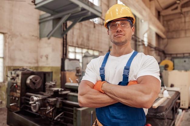 Спортивный мужчина-строитель в строительном шлеме, стоящий в мастерской