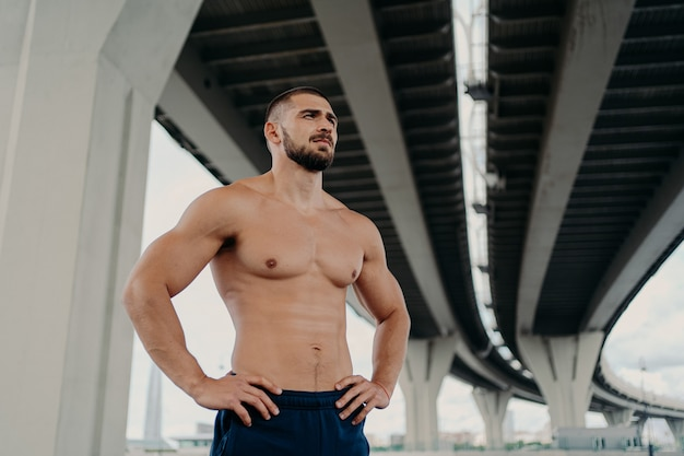 Athletic male fitness model keeps hands on waist poses with muscular perfect naked body, looks seriously into distance, does sport exercises outdoor, focused somewhere, goes in for sport regularly