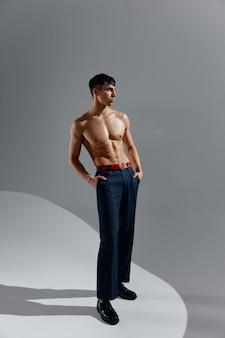 ジーンズと靴のアスリート男性モデル裸の胴体ボディービルダーフィットネス