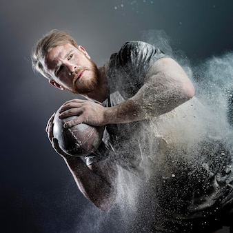 Athletic male rugby player holding ball with dust