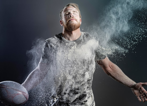 Athletic male rugby player holding ball with powder