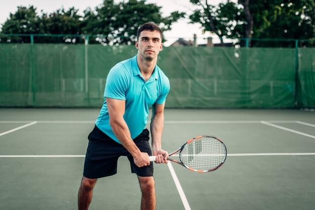 アスレチックの男性テニスプレーヤーが屋外コートで遊ぶ
