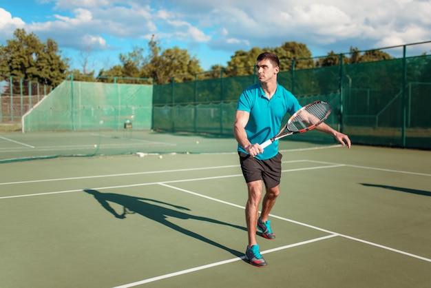 Спортивный мужской теннисист играет на открытом корте