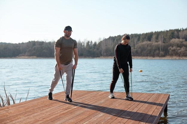 Атлетик мужчина и женщина выполняют упражнения с расширителем на пирсе на берегу озера. здоровый образ жизни, спорт, тренировки