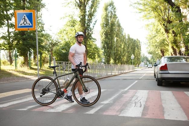 Athletic man in bike helmet crossing street on crosswalk with his bicycle