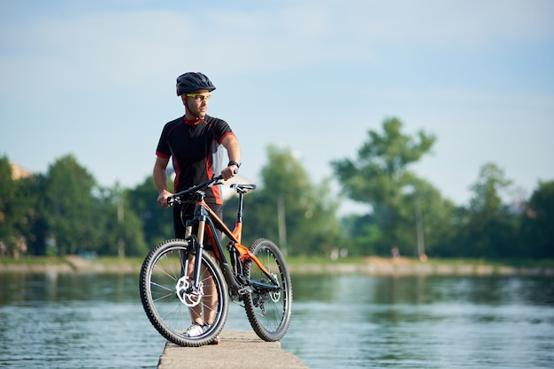 Атлетик байкер возле велосипеда смотрит далеко думая о будущих успехах и достижениях