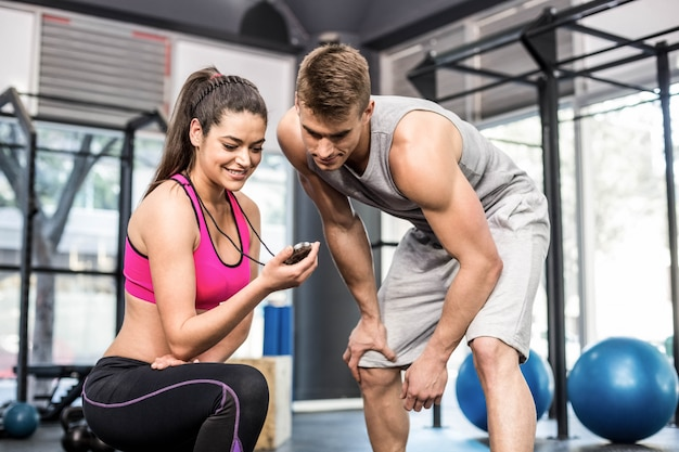 Athletic man checking time with trainer woman at gym