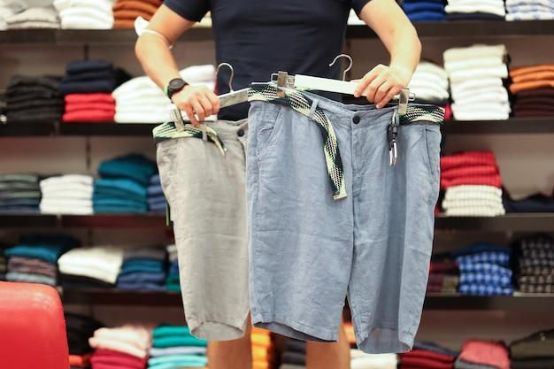 アスリートの男性は、快適な夏の男性の服のコンセプトを選択して夏の新しいショーツを選択します