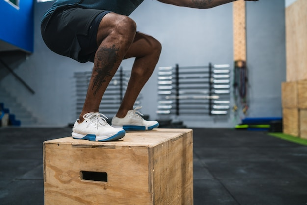 Athletic man doing box jump exercise.