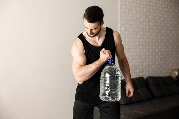 Athletic man doing calf raise exercises with big bottle of water. white modern room on background. strong man in black sportswear excercising to have a fit body.