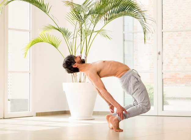 Athletic man doing a calisthenics backbend balance pose to stretch and strengthen his muscles in a high key gym with copyspace in a health and fitness concept