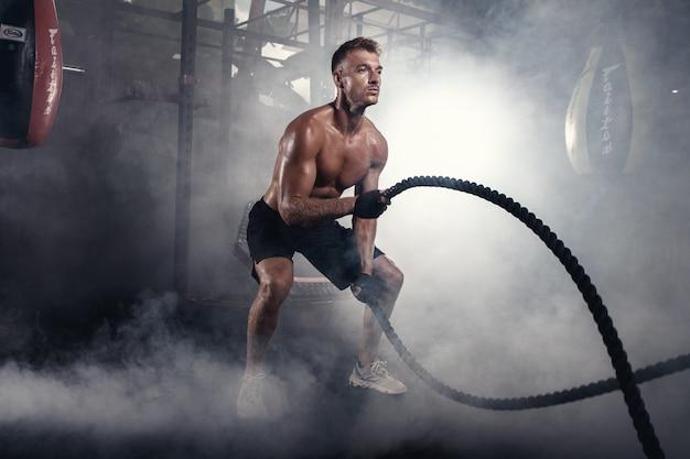 연기가 자욱한 체육관에서 로프로 크로스 핏 운동을하는 운동 남자