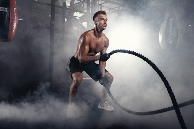 Athletic man doing crossfit exercises with rope in smoky gym