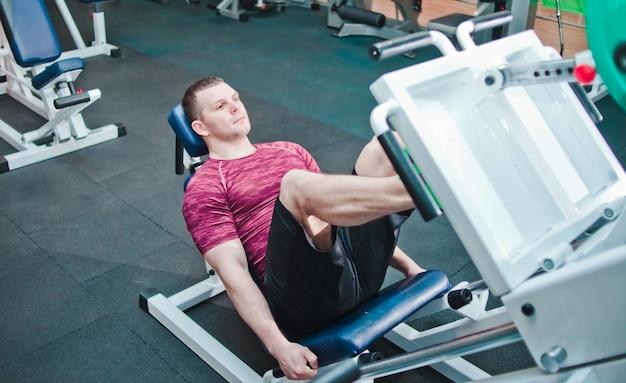 Athletic man doing exercise press leg machine in gym.