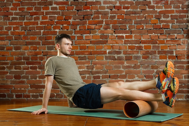 Athletic man doing exercises for the balance on rubber ball with gymnastic stick