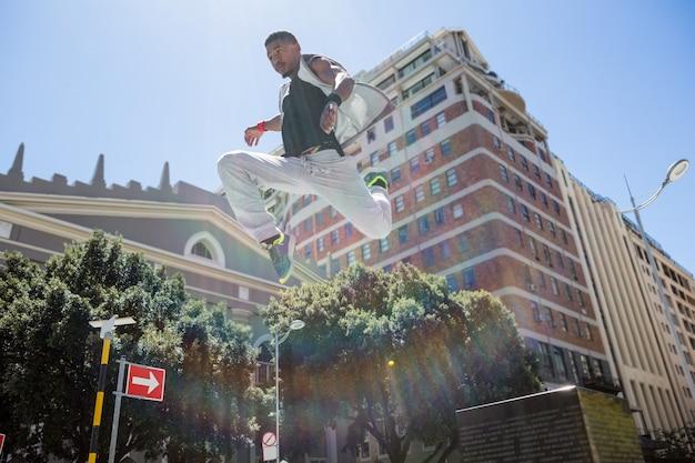 Спортивный мужчина делает паркур в городе