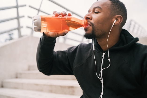 Athletic man drinking something after training