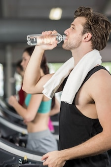 Athletic man drinking water while running on treadmill in gym