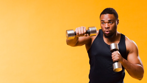 Athletic man exercising with weights