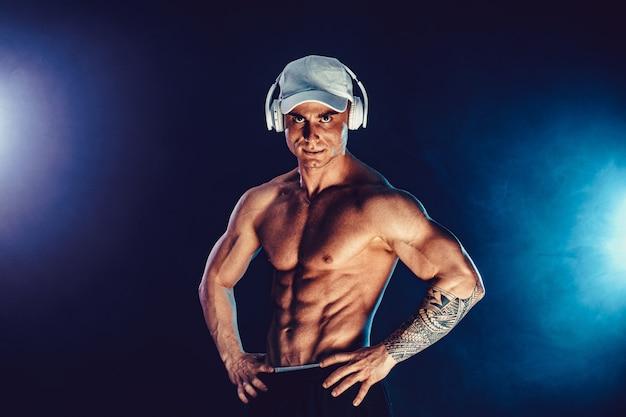 Спортивный (ый) мужчина сгибает мышцы в темноте с дымом. сильный бодибилдер с идеальным прессом.