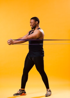 Athletic man in gym outfit exercising with resistance band