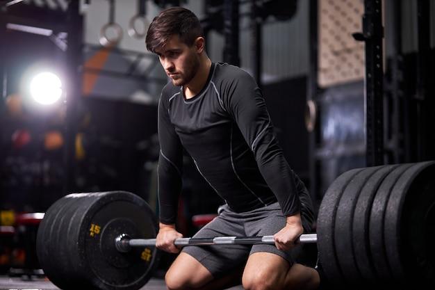 暗いジムやフィットネスクラブでバーベルの重みでトレーニングやボディービルをしている運動選手。スポーツウェアのトレーニングだけで若い白人の男。スポーツ、クロスフィット、ボディービルのコンセプト