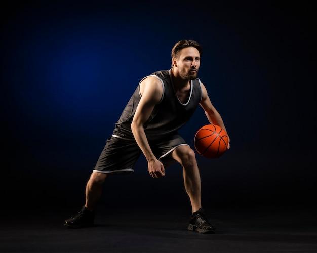 Спортивная (ый) мужчина держит баскетбол