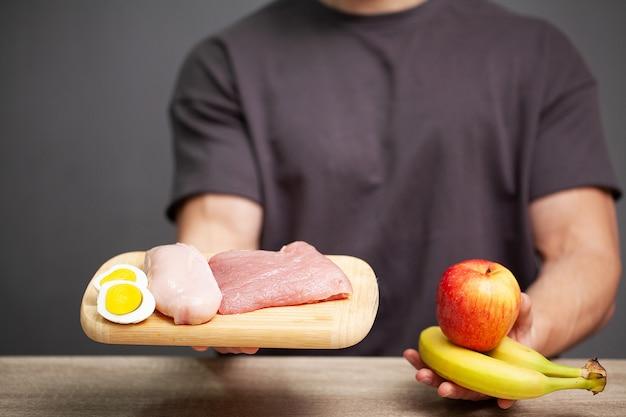 アスリートの適切な栄養のために肉とボードを保持している運動の男