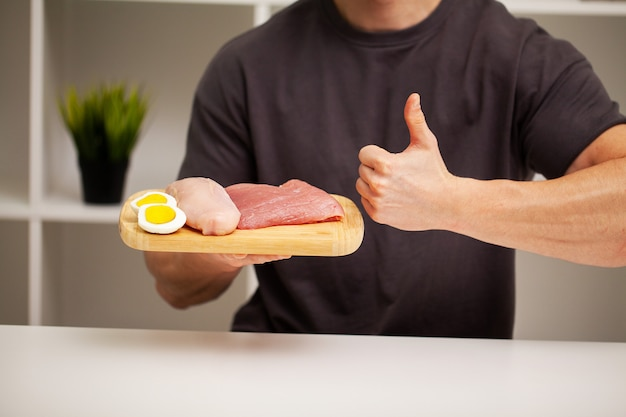 Athletic man holding a board with meat for proper nutrition of the athlete