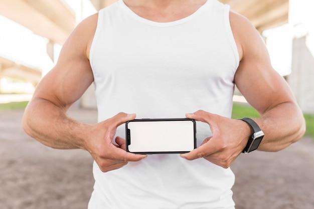 空の画面で彼の携帯電話を保持している運動の男