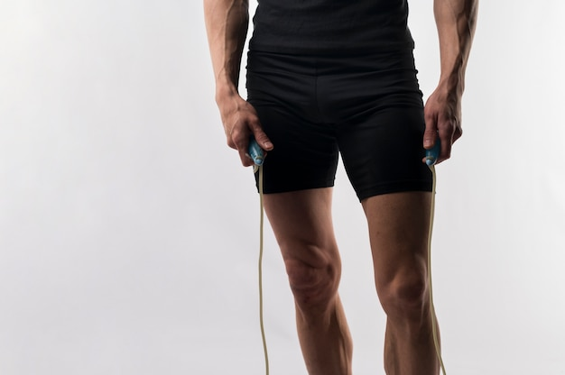 Athletic man holding jumping rope