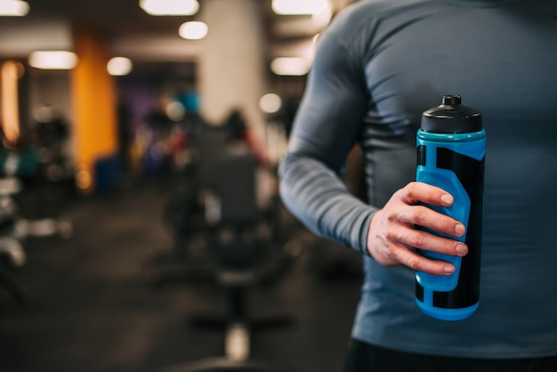 Athletic man holding water bottle in the hand in the gym, close-up.