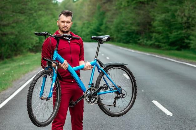 トラックスーツを着たアスレチック男が森の道に立っている間、彼の肩に自転車を抱えています。健康的なライフスタイルのコンセプト、カーディオトレーニング。 copyspace。