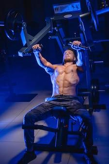 バーベルベンチプレスで運動しているジムの運動選手。完璧なボディを持つボディービルダー。青いフィルター。上からの眺め。裸の胴体。