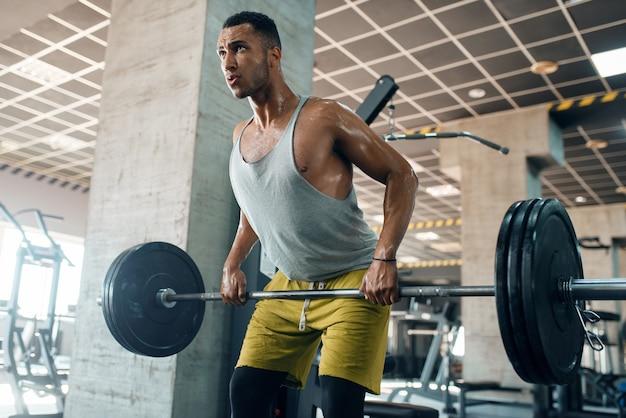 ジムでトレーニングにバーベルで運動を行うスポーツウエアで運動の男。