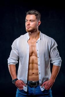 Спортивный (ый) мужчина в белой расстегнутой рубашке позирует на темном фоне.