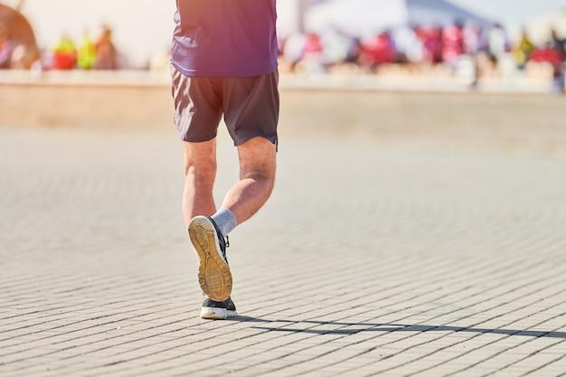 都市道路でスポーツウェアでジョギングアスリート男