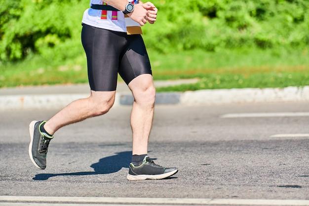 Спортивный человек, бегающий в спортивной одежде на городской дороге