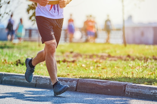 Спортивный человек, бег в спортивной одежде на городской дороге