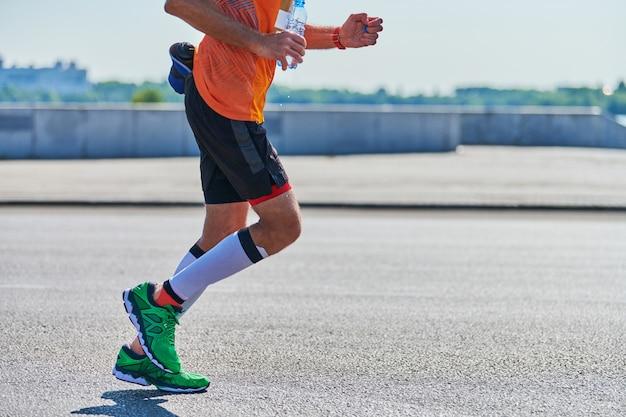 Спортивный человек, бег в спортивной одежде на городской дороге Premium Фотографии