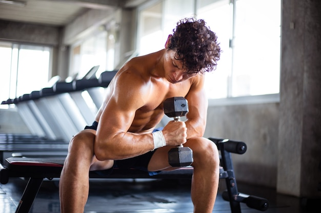 Athletic man lifting dumbbell for bodybuilding in fitness