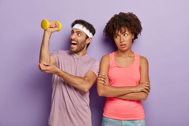 운동 남자는 아령을 들어 올리고 피곤한 운동을하고 머리띠와 티셔츠를 입고 불행한 지루한 여자가 팔을 접은 채 서 있습니다.