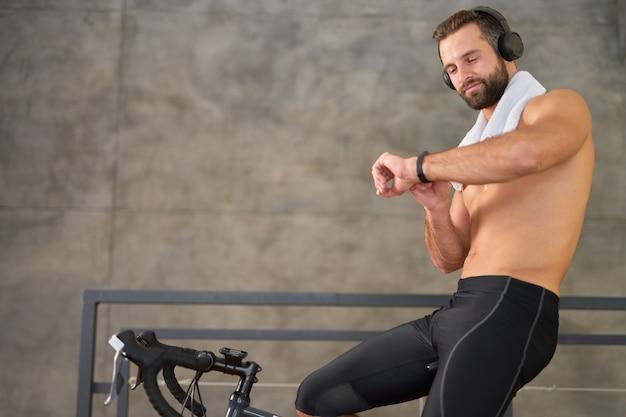 Спортивный (ый) мужчина смотрит на фитнес-трекер во время тренировки