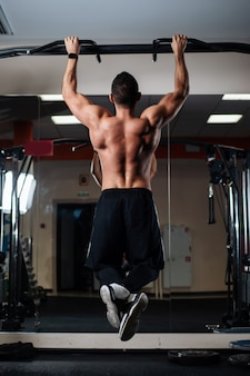 Athletic man making pull-up exercises on a crossbar in the gym
