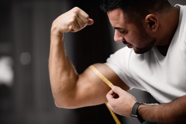 Athletic man measures his bicep with a measuring tape.
