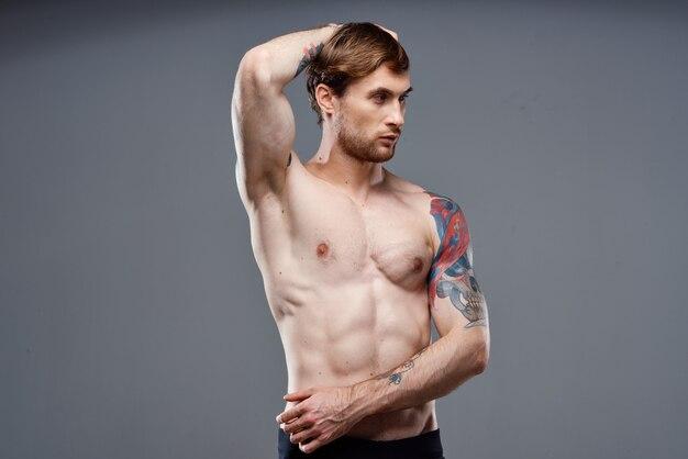 彼の腕に運動選手の筋肉の体のトレーニングの入れ墨
