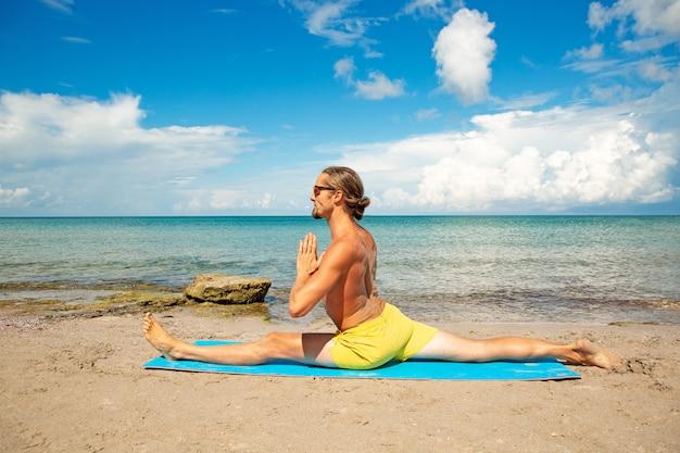 フィットネスヨガの練習をしているビーチで運動の男。強さとバランスのアクロヨガ要素。