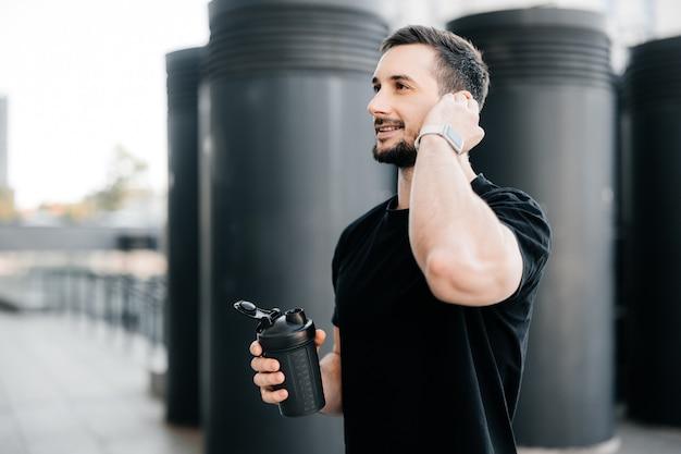 アスリートの男性は、電話に出るためにトレーニングを一時停止します。ジョギングの後に休んでいる間、クライアントと電話で話しているフレンドリーな男。屋外での朝のトレーニング。